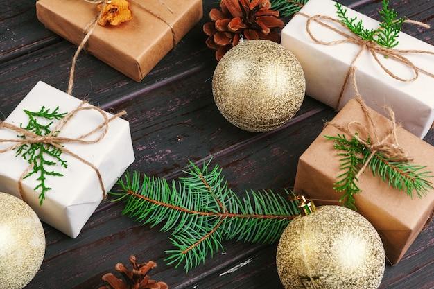 크리스마스 구성입니다. 크리스마스 선물, 니트 담요, 소나무 콘, 나무 배경에 전나무 가지.