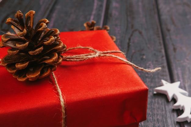 크리스마스 구성. 크리스마스 선물, 니트 담요, 소나무 콘, 나무 배경에 전나무 가지