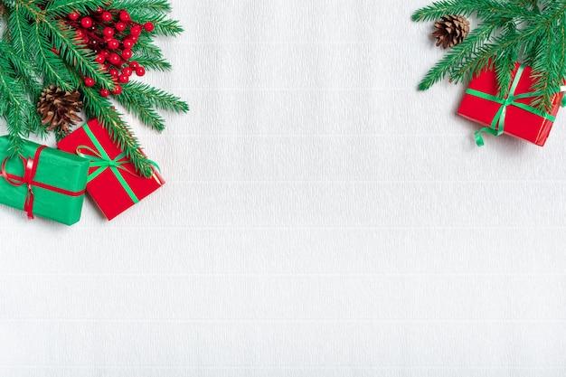 クリスマスの組成物。クリスマスプレゼント、松ぼっくり、白い段ボール紙の背景にモミの枝。トップビュー、コピースペース。