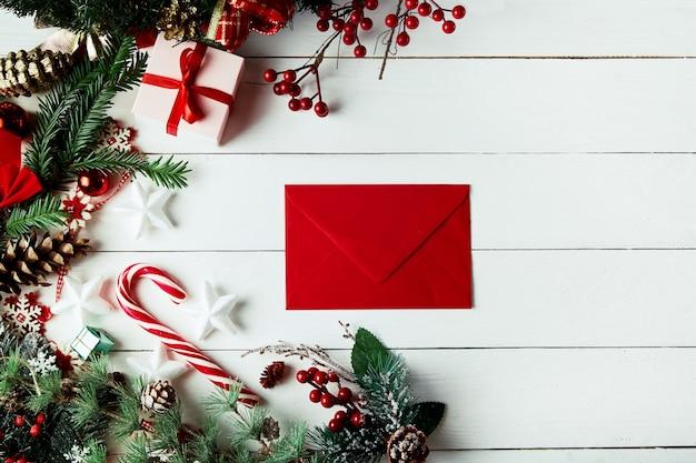 Новогодняя композиция. рождественский подарок, сосновые шишки, еловые ветки на деревянных белом фоне.