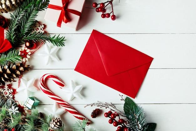 クリスマス作曲。クリスマスプレゼント、松ぼっくり、木製の白い背景の上のモミの枝。