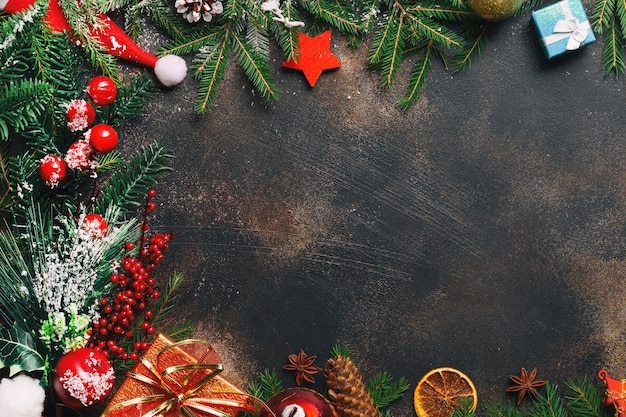 Christmas composition. christmas gifts, pine branches, toys, anise stars, santa hat on stone background with free space and snow. flat lay, top view.