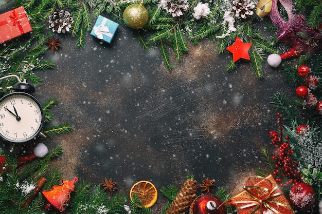 Christmas composition. christmas gifts, pine branches, toys, vintage clock, anise stars, santa hat on stone background with free space and snow. flat lay, top view.