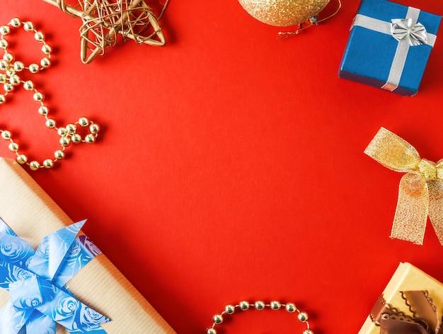 크리스마스 구성. 크리스마스 선물, 소나무 가지, 빨간색 배경에 트리 장식. 평면 평신도, 평면도.
