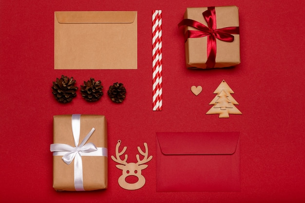 Christmas composition. christmas gifts, wooden toys, pine cones on red background top view