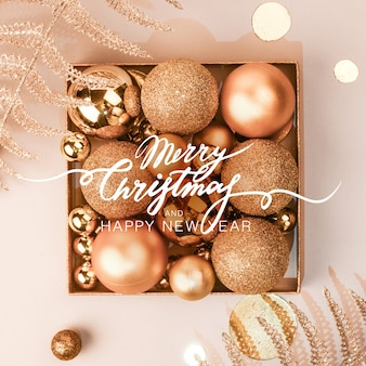 Новогодняя композиция. рождественские золотые украшения, шары и блестящие декоративные растения на светлом пастельном фоне. плоская планировка. скопируйте пространство. стильная композиция в стиле минимализма.