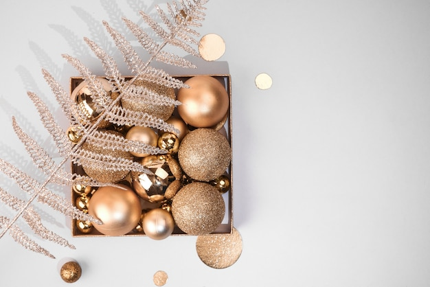 Christmas composition. christmas golden decorations, balls and shiny decorative plants on a light pastel background. flat lay. copy space. stylish composition in a minimalist style.