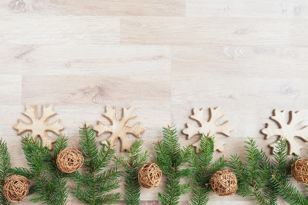 Christmas composition.  christmas ornaments, spruce branches,  wooden snowflakes and gold  braided balls  on light wooden background. flat lay, top view, copy space for text