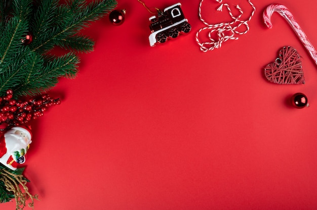 Christmas composition. christmas red decorations, christmas tree branches on red background. flat lay, top view, copy space.