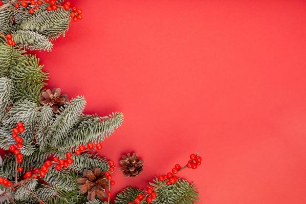 クリスマスの作文。クリスマスの赤い装飾、赤い背景にバンプとモミの木の枝。フラットレイ、上面図、コピースペース。
