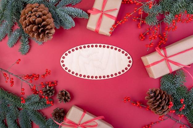 クリスマスの作文。クリスマスの赤い装飾、赤い背景におもちゃのギフトボックスとモミの木の枝。フラットレイ、上面図、コピースペース。