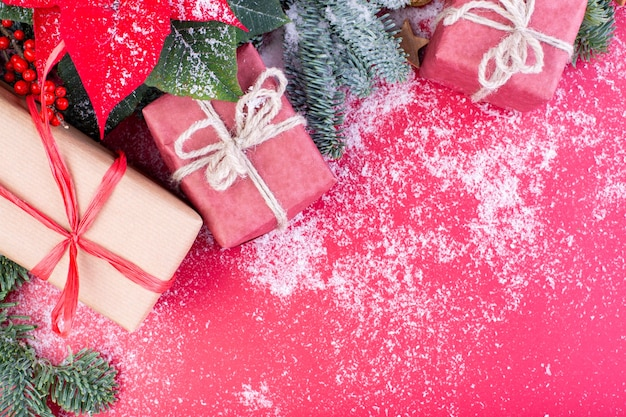 Новогодняя композиция. рождественские красные украшения, еловые ветки с игрушками подарочные коробки на красном фоне. плоская планировка, вид сверху, копия пространства.