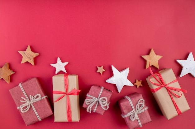 クリスマスの組成物。赤いクリスマスの装飾、星、赤い背景の上のギフトボックス。フラットレイアウト、トップビュー、テキスト用のスペース