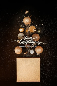 Christmas composition. christmas tree concept with golden decorations, balls, glitters on a black background. background. christmas, new year concept. minimalism flat lay