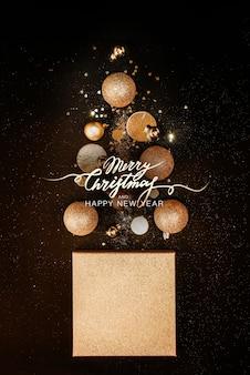 クリスマスの組成物。金色の装飾、ボール、クリスマスツリーのコンセプトは、黒の背景に光ります。バックグラウンド。クリスマス、新年のコンセプトです。ミニマリズムフラットレイアウト