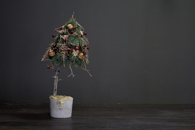 Christmas and  composition. christmas tree made of fir branches and decorated by natural materials and balls in a cement pot