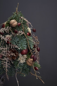 Christmas and  composition. christmas tree made of fir branches and decorated by natural materials and balls on dark