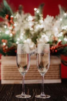 金色のライト、花輪、おもちゃ、空のシャンパングラスで飾られたクリスマスコンポジションのクリスマスツリー。