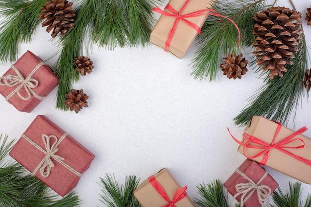 크리스마스 구성. 크리스마스 화이트 장식, 흰색 바탕에 장난감 선물 상자 전나무 나무 가지. 평면 위치, 평면도, 복사 공간, 인사말 카드