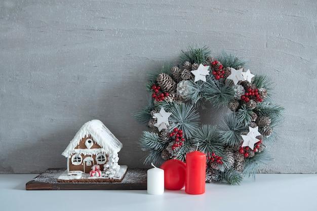 クリスマスの構成:灰色の背景にクリスマスリース、キャンドル、ジンジャーブレッドハウス。