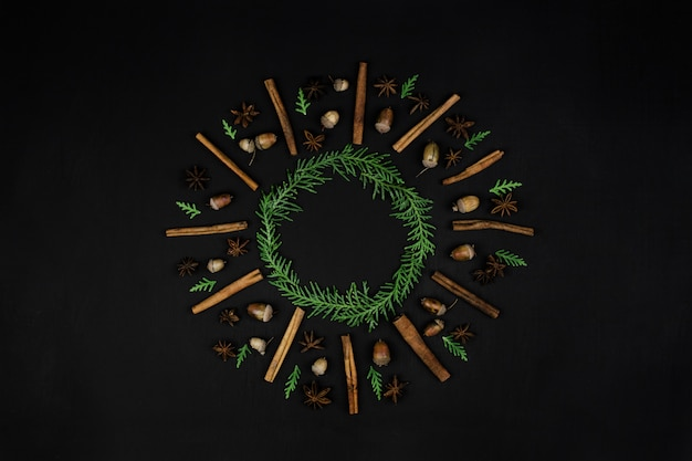 Christmas composition. christmas wreath  from pine branches, cinnamon stick, anise star, acorns on a black background. flat lay, top view, copy space, square
