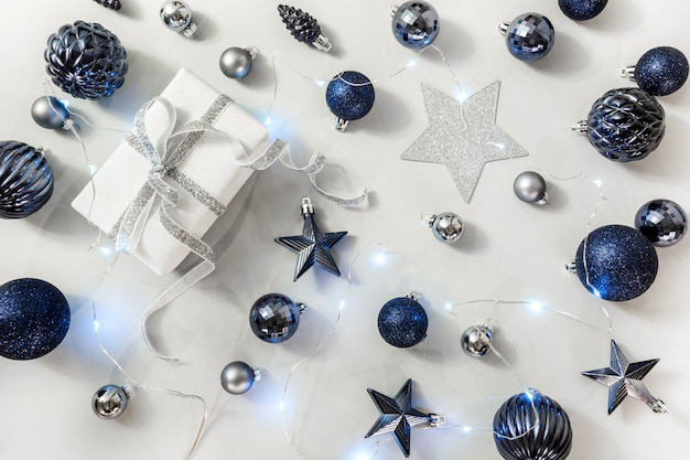 Christmas composition of classic blue balls and giftbox on grey