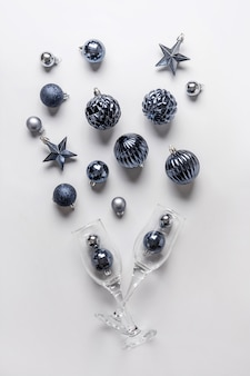 Christmas composition of classic blue balls and glasses of champagne on grey.