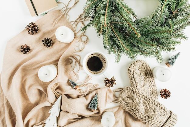 크리스마스 구성. 커피 잔, 전나무 가지의 화환 프레임, 니트 장갑, 베이지 색 담요 및 장식. 평면 위치, 평면도