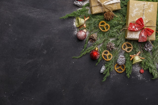 Christmas composition of coniferous branches, decorations and sweets on dark background. flat lay. top view nature new year concept. copy space.