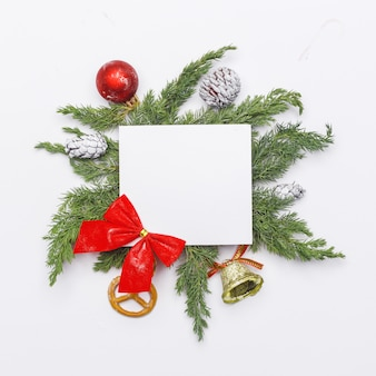 Christmas composition of coniferous branches, decorations and sweets on light background. flat lay. top view nature new year concept. copy space.