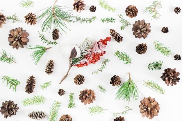 クリスマスの組成物。針葉樹の木の枝、火の円錐形、白のヒイラギの実。クリスマス、冬、。フラット横たわっていた、トップビュー