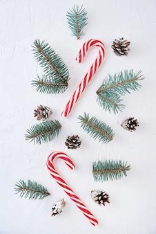 クリスマス作曲。白い背景にモミの木の枝、松ぼっくり、お菓子で作られた装飾