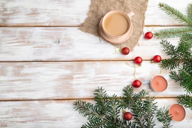 크리스마스 구성. 장식, 빨간 공, 전나무와 가문비 나무 가지, 커피 한잔, 흰색 나무 테이블에 촛불. 평면도.