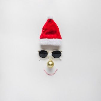 Christmas composition of face from santa hat and sunglasses