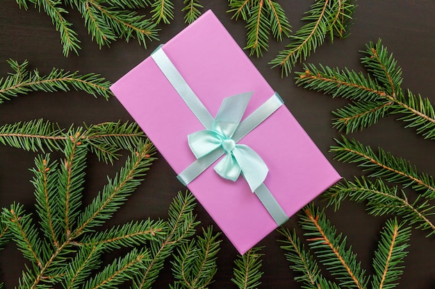 暗い背景の上のクリスマス作曲モミの枝とギフトボックス