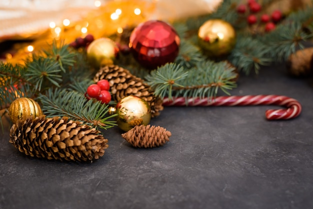Christmas composition of fir branches, garlands of gold, christmas balls and candy, pine cones.