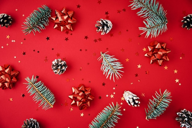 Christmas composition. fir branches, pine cones and festive confetti on a red background, top view