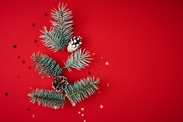 Christmas composition. fir branches in shape of christmas tree with festive confetti on red background with copy space