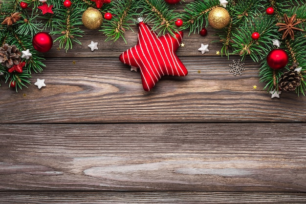 Christmas composition. fir tree branches, gift boxes, decorations, pine cones on wooden background