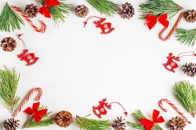 크리스마스 구성. 전나무 나무 가지, 빨간 나무 크리스마스 장난감, 활, 흰색 바탕에 사탕 지팡이.