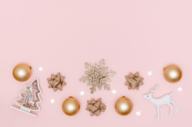 Christmas composition. frame from golden balls, white stars, snowflake, christmas tree, gift bows, deer on pastel pink paper background. top view, flat lay, copy space.