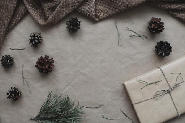 Новогодняя композиция в рамке из еловых и сосновых веток и шишек на бумажном фоне ...