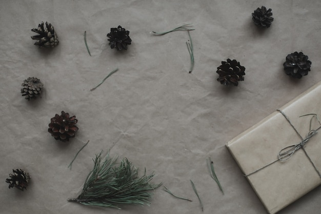 クラフト紙の背景にモミと松の木の枝と円錐形で作られたクリスマスの構成フレーム...