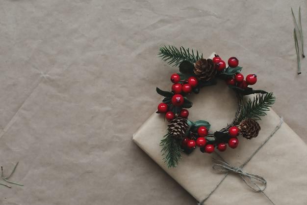 Новогодняя композиция из еловых и сосновых веток и шишек на фоне крафт-бумаги f ...