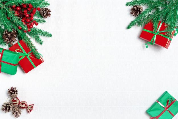 크리스마스 구성. 전나무 나무 가지, 흰색 바탕에 소나무 콘으로 만든 프레임.