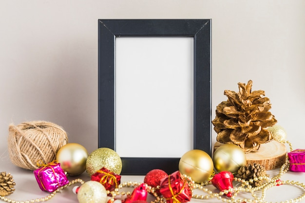 Christmas composition of frame with baubles on table