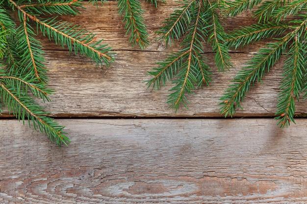 木製の背景にモミの枝とクリスマス作曲フレーム