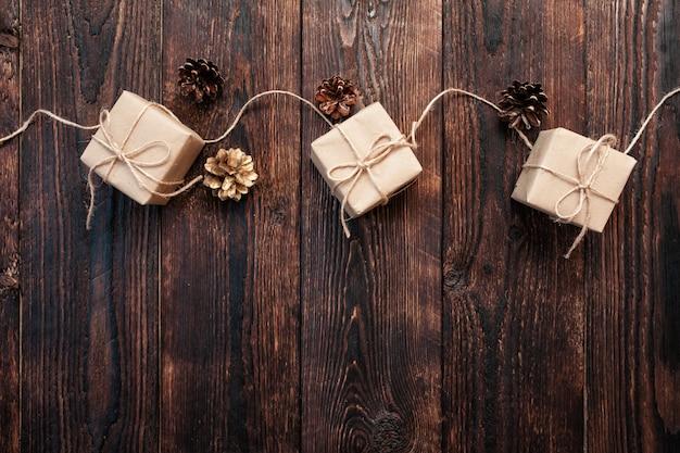 나무 배경에 있는 선물 상자와 콘으로 만든 크리스마스 구성