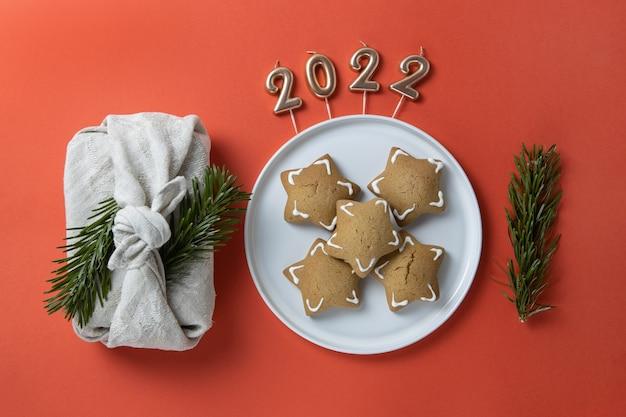 빨간색 배경에 접시 2022 촛불에 크리스마스 구성 보자기 선물 포장 진저
