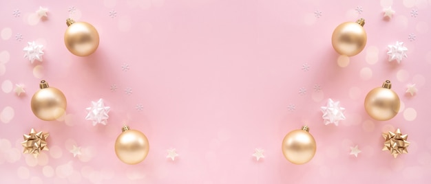 Christmas composition. gift, baubles, greeting card, golden decorations on pastel pink surface.